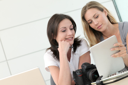 Women photographers working in office with tablet